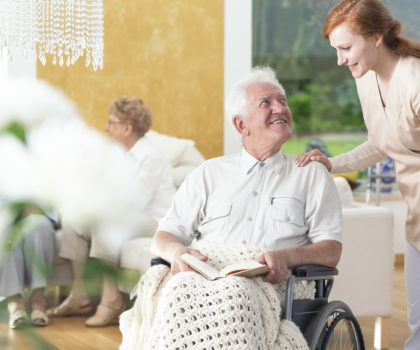 A man in his old age ia a wheelchair talking to a personal assistant in a common room of a rehabilitation center.